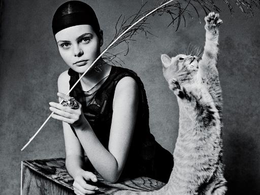 Retro-Fotoshooting: Frau hält Pfauenfeder, Katze spielt damit.